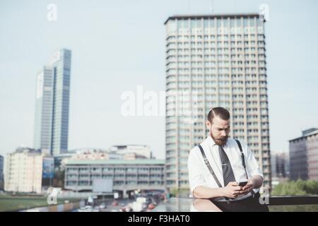 Stylish businessman reading smartphone text update on office balcony - Stock Photo
