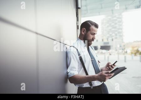 Stylish businessman using smartphone and digital tablet outside office - Stock Photo