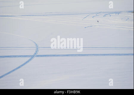 Lonesome man and snowmobile tracks on frozen lake in Sotkamo, Finland. - Stock Photo