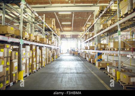 Forklift trucks and drivers working in distribution warehouse aisle - Stock Photo