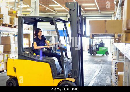 Female forklift truck driver working in distribution warehouse - Stock Photo