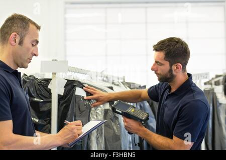 Warehouse workers using barcode scanner on garment stock in distribution warehouse - Stock Photo