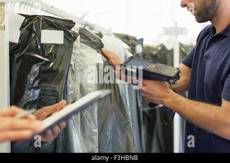 Cropped view of warehouse workers using barcode scanner on garment stock in distribution warehouse - Stock Photo