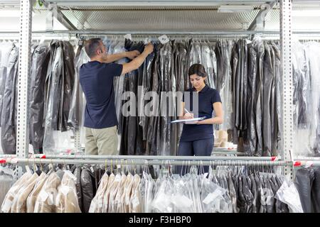 Two warehouse workers preparing garments in distribution warehouse - Stock Photo