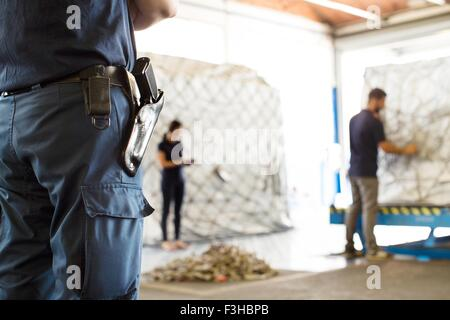 Security guard watching workers in air freight warehouse - Stock Photo