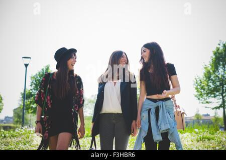 Three young female friends chatting whilst strolling in park - Stock Photo