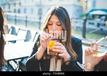 Young woman and friends drinking cocktails at waterfront cafe - Stock Photo