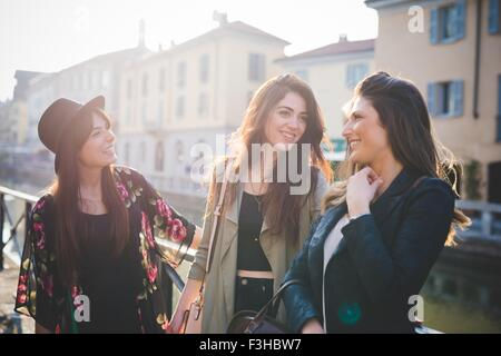 Three young women chatting on canal waterfront - Stock Photo