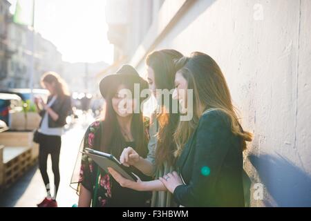 Three young women using digital tablet on city street - Stock Photo