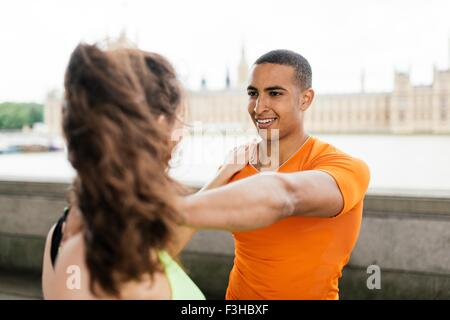 Over shoulder view of male and female runners warming up on riverside - Stock Photo