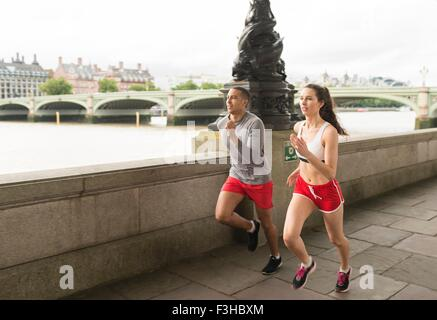 Male and female runners running on Southbank, London, UK - Stock Photo