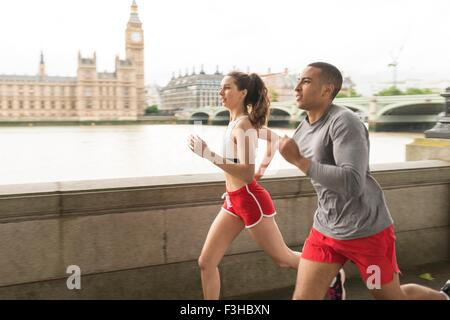 Male and female runners running along Southbank, London, UK - Stock Photo