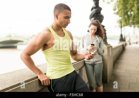 Male and female runners texting on smartphone at riverside - Stock Photo