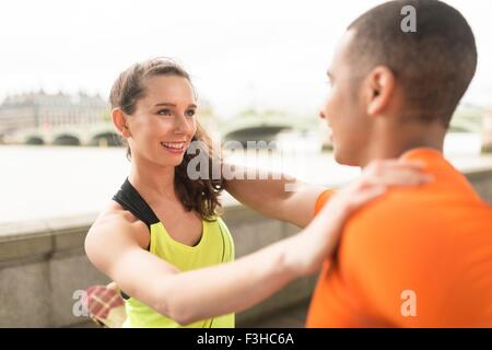 Young male and female runners warming up at riverside - Stock Photo