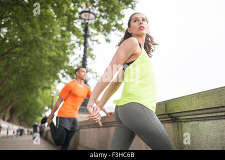 Young male and female runners warming up on riverside - Stock Photo