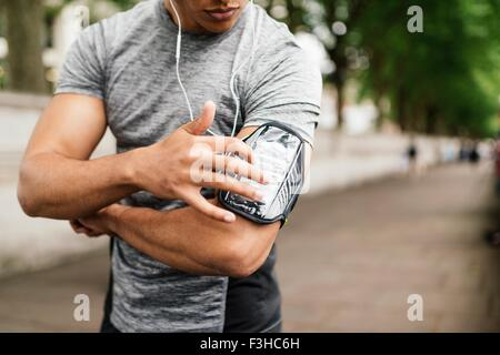 Cropped shot of male runner choosing music on smartphone - Stock Photo