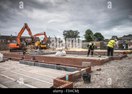 Workers laying bricks on construction site - Stock Photo