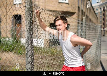 Runner stretching against wire fence, Wapping, London - Stock Photo