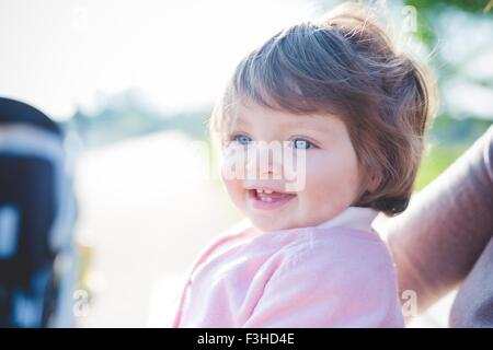 Close up portrait of blue eyed female toddler in park - Stock Photo