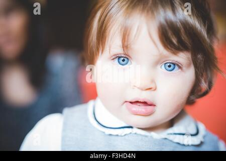Close up portrait of female toddler with blue eyes - Stock Photo