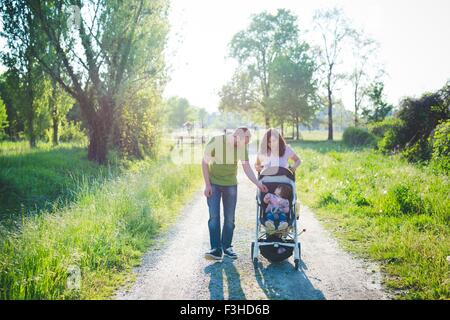 Mid adult couple with toddler daughter in pushchair strolling in park - Stock Photo