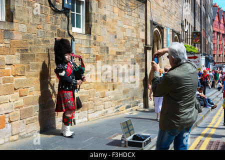 EDINBURGH, SCOTLAND - JUNE 11, 2015: Scottish Bagpiper playing his bagpipe in the Old Town of Edinburgh in Scotland - Stock Photo