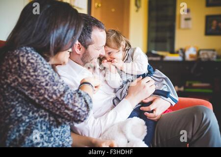 Shy female toddler sitting on fathers lap in living room - Stock Photo