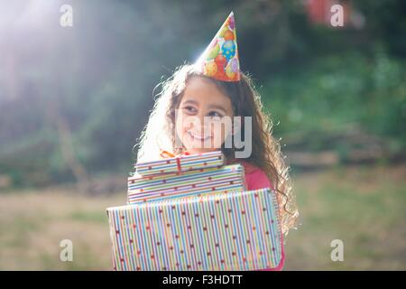 Girl carrying stack of gifts at garden birthday party - Stock Photo