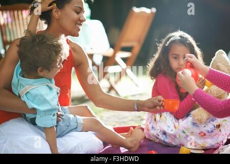 Mother and children playing picnics at garden birthday party - Stock Photo