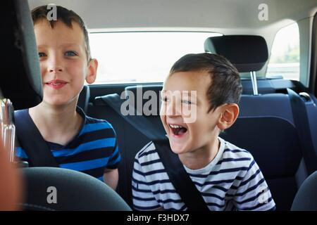Two happy young brothers traveling in car back seat - Stock Photo