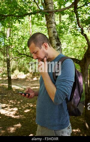 Male hiker looking down at smartphone in forest - Stock Photo