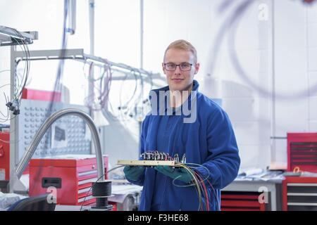 Portrait of apprentice electronics worker in electronics factory, - Stock Photo
