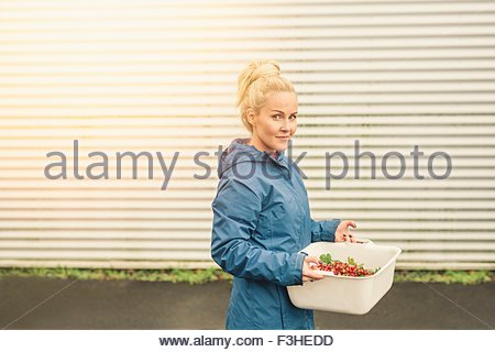 Mid adult woman holding container of redcurrants, outdoors - Stock Photo
