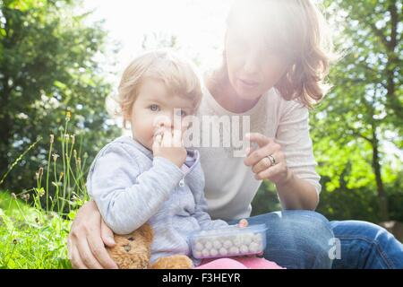 Mother and female toddler eating sweets in park - Stock Photo