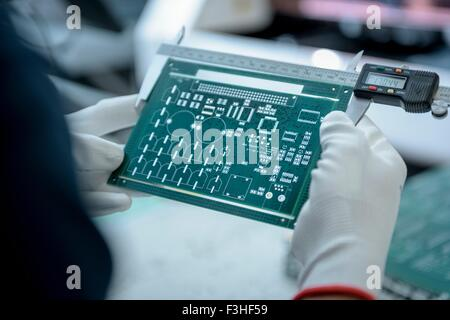 Worker measuring cut circuit board in circuit board factory, close up - Stock Photo