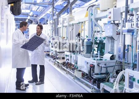 Workers inspecting circuit board by processing plant in circuit board factory - Stock Photo