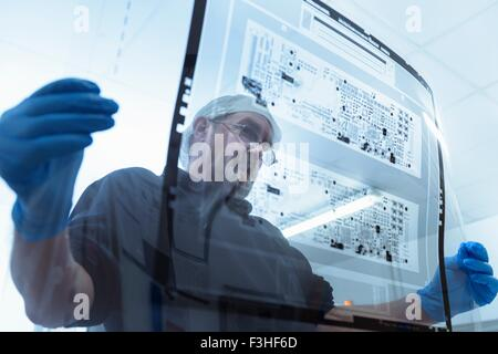 Worker inspecting circuit board negative sheet in circuit board factory - Stock Photo