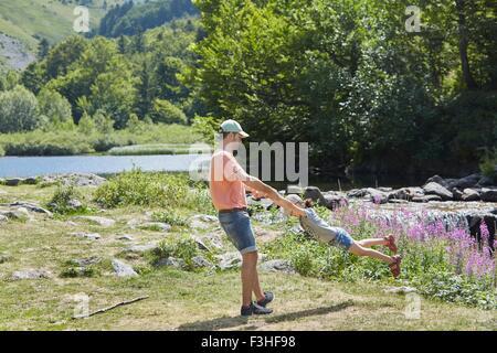 Father and daughter having fun by stream, Saut Deth Pish, Valle de Aran, Spain - Stock Photo
