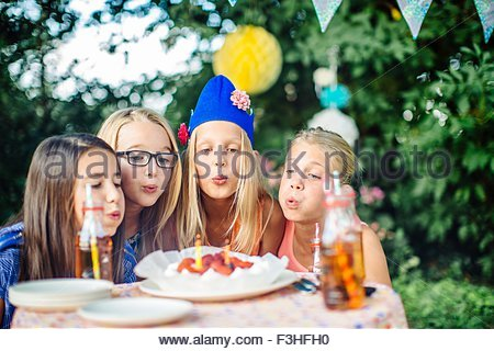 Girls blowing out candles on birthday cake at summer garden party - Stock Photo