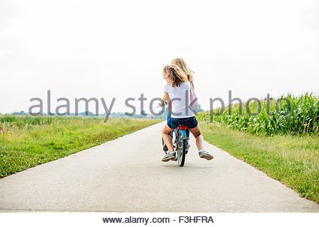 Rear view of two tween girls cycling along rural road - Stock Photo