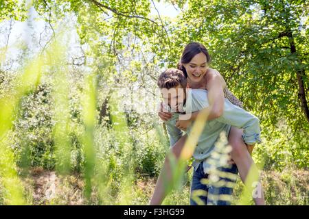 View through foliage of young man giving young woman piggyback - Stock Photo