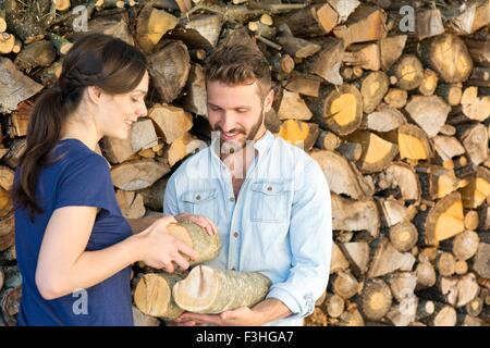Young couple selecting chopped firewood from pile - Stock Photo