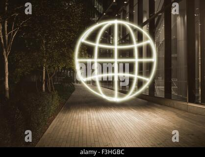 Glowing globe symbol in city at night - Stock Photo