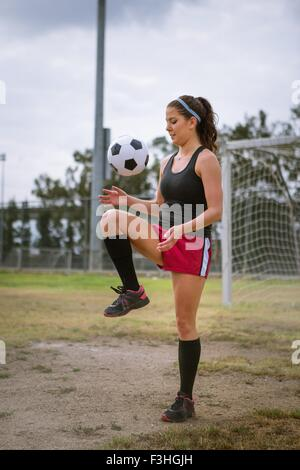 Soccer player bouncing ball on knee in field - Stock Photo