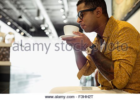 Young man drinking coffee in coffee shop - Stock Photo
