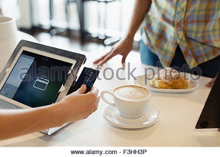 Customer paying for coffee in coffee shop, mid section - Stock Photo