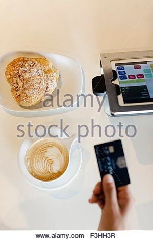 Customer paying for coffee in coffee shop, overhead view - Stock Photo