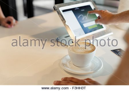 Customer paying for coffee in coffee shop, signing signature on digital transaction technology - Stock Photo