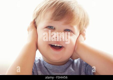 Portrait of young boy covering ears with hands, looking away smiling - Stock Photo