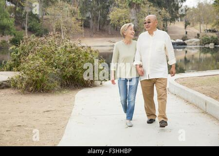 Senior couple walking along pathway, holding hands - Stock Photo